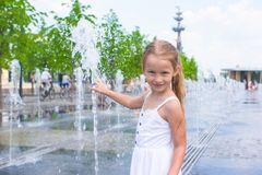 Little girl have fun in outdoor fountain at hot Stock Images