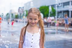 Little girl have fun in outdoor fountain at hot Royalty Free Stock Photo