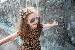 Little girl have fun walking near the waterfall. Little girl in a leopard dress have fun walking near the waterfall royalty free stock image