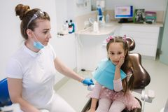 Little girl have a toothache. Dentist will help to the patient royalty free stock image