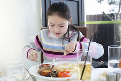 Little girl having a big breakfast Royalty Free Stock Photo