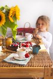 The little girl is having breakfast at home. On the table is a bouquet of flowers of sunflowers and a sweet pie with fruit, stock image