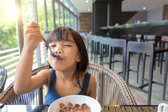 Little girl having breakfast on table Stock Photo