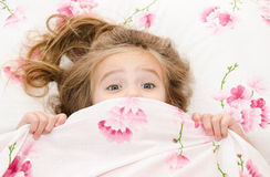 Little girl having childhood nightmares. And fears hiding under the quilt royalty free stock image