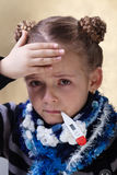 Little girl with the flu checking her temperature Stock Image