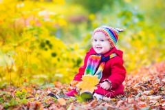 Little girl having fun in an autumn park Stock Photos
