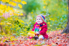 Little girl having fun in an autumn park Royalty Free Stock Photos