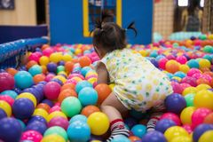 Little girl having fun in ball pool. Rare shot of little girl crawling and having fun in ball pit with colorful balls. Child playing on indoor playground. Asian royalty free stock photos