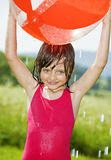 Little girl having fun with ball and rain Stock Photo