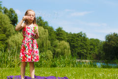 Little girl having fun blowing soap bubbles in park. Royalty Free Stock Photo
