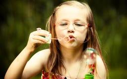 Little girl having fun blowing soap bubbles in park. Stock Image