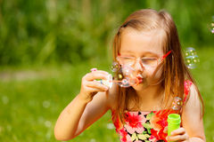 Little girl having fun blowing soap bubbles in park. Royalty Free Stock Image