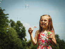 Little girl having fun blowing soap bubbles in park. Stock Photo
