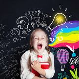 Little girl having fun with book on school background. With lightbulb, arts and science stock photography