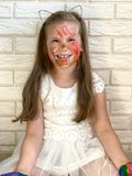A little girl is having fun, colored paint on her hands. royalty free stock images