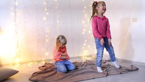 Little girl having fun and dancing for music, second girl sits angry on floor. Little dark-haired girl dancing and having fun at music, other girl with light stock video footage