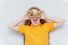 Little girl having fun with donuts eyes. Little curly girl having fun with donuts eyes royalty free stock photo