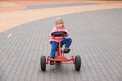 Little girl having fun driving a pedal car in day. stock image