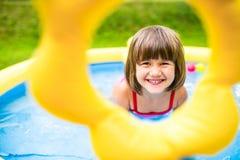 Little girl having fun in the garden swimming pool. Stock Photography