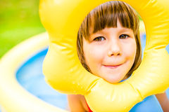 Little girl having fun in the garden swimming pool. Royalty Free Stock Photos