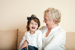 Little girl having fun with grandma on the sofa Stock Photo