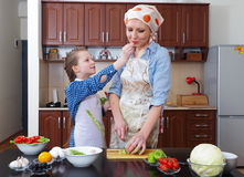 Little girl is having fun with  her mother at kitchen Stock Photos