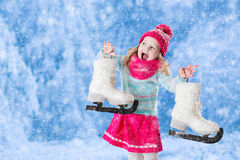 Little girl having fun at ice skating in winter. Happy laughing little girl having fun ice skating in snowy park. Winter sport and outdoor activity for family Stock Photos