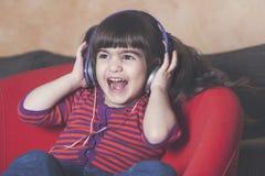Little girl having fun listening to music Stock Photography