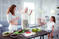 Little girl having fun with mom and grandmother while cooking salad stock photos