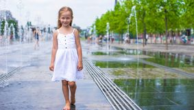 Little girl having fun in outdoor fountain at hot Stock Photos