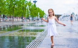 Little girl having fun in outdoor fountain at hot Stock Photography