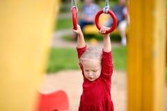 Little girl having fun on outdoor playground. Summer active sport leisure for kids. Kindergarten or school yard. Little child royalty free stock photography