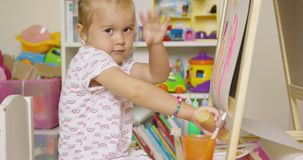 Little girl having fun painting with water colors stock footage