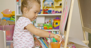 Little girl having fun painting with water colors Royalty Free Stock Photos