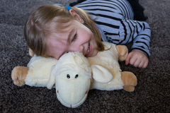 Little girl having fun on a pillow in the shape of sheep. Royalty Free Stock Photos