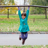 Little girl having fun on playground gymnastics bar Stock Photos