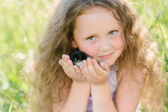 Little girl having fun playing with duck or chicken. Toddler kids outdoor. Happy child laughing and smiling Stock Photo