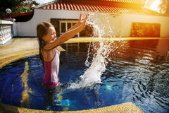 Little girl having fun in the pool. Royalty Free Stock Images