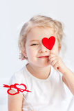 Little girl having fun with a red heart Stock Photography