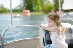Little girl having fun on a sailboat Stock Images