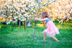 Little girl having fun on scooter in blooming apple tree garden on spring day Stock Photo