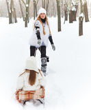 Little girl having fun on a sleigh with her mother Royalty Free Stock Images