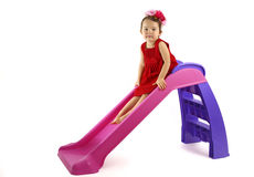 Little girl having fun on slide isolated Stock Image