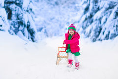 Little girl having fun in snowy winter park Stock Images