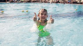 Little kid girl swim in a swimming pool clear water on summer resort stock footage