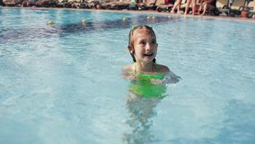 Little girl having fun in a swimming pool, first time learning to swim, spending summer holidays on a beach resort stock footage