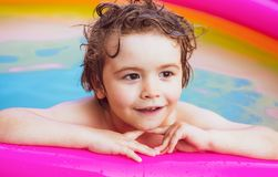 Little girl having fun in swimming-pool. Happy child having fun at swimming pool on sunny day. Children playing in pool. Kids Swimming Pool Concept stock images