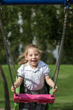 Little Girl Having Fun on a Swing in a Green Park Stock Photography