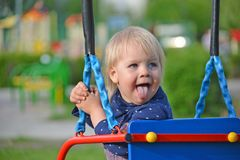 Little girl having fun on a swing outdoor Stock Image