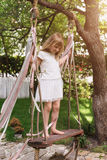 Little girl having fun on a swing outdoor. Child playing, garden playground. Royalty Free Stock Images